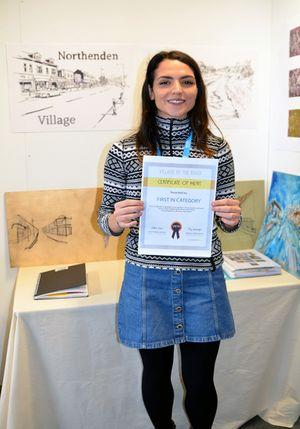 Faye and her certificate in front of the work she did to promote Northenden Village